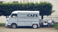 uam imagem de um caminão azulparado na rua escrito café em sua lataria
